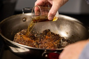 Pouring brandy onto steaks